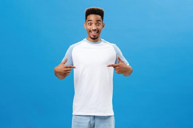 Очаровательный темнокожий парень спрашивает совета, что надеть на свидание, указывая на футболку с веселым счастливым выражением ...