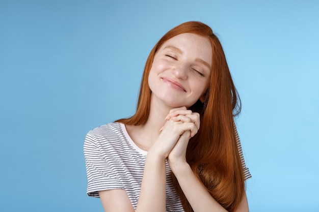 Charming delighted happy dreamy redhead girlfriend ginger long hair tilting head close eyes smiling pleased daydreaming thinking about sweet tender memories press palms together, blue background.