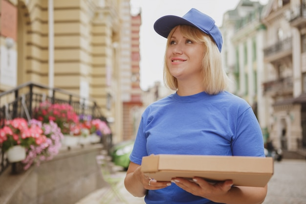 Charming delivery woman with pizza box