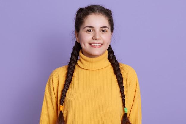 黄色いセーターを着て、ライラックの壁にポーズをとって2つのおさげ髪の魅力的なくぼみのある若い女性