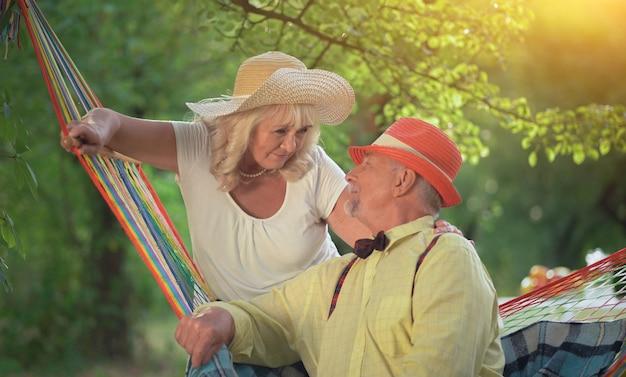 夏の庭で休んでいる魅力的な老夫婦