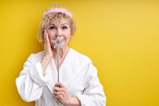 머리에 왕관을 쓰고 목욕 가운에 매력적인 노인 여성, 손에 magica 지팡이를 들고, 수석 요정, 놀람으로 얼굴 뺨을 만지고