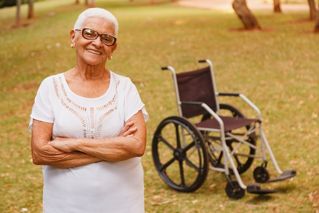 휠체어와 함께 서있는 공원에서 웃는 매력적인 노인 여성은
