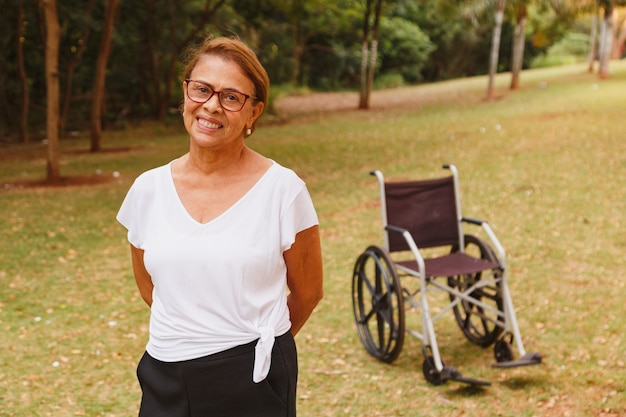 Charming elderly woman smiling in the park standing with the wheelchair in the