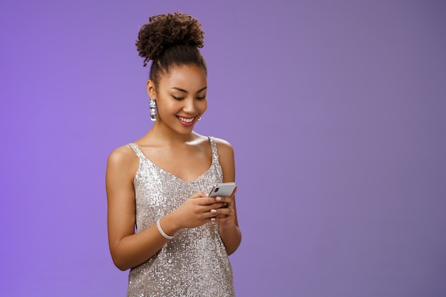 Очаровательная элегантная афро-американская женщина в стильном блестящем платье для выпускного вечера пишет сообщение, звонит другу, держит смартфон, выглядит забавно, счастливая улыбка на дисплее телефона с помощью приложения для гаджета, прокручивает фотографии вечеринки.