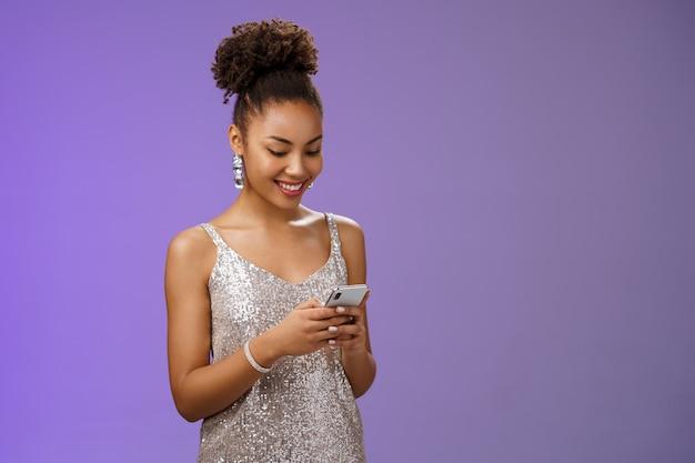 Affascinante donna afro-americana elegante in elegante abito da ballo scintillante che scrive messaggio chiamando amico tenere smartphone guardare divertito sorriso felice display del telefono utilizzando l'app gadget scorrere le foto della festa.