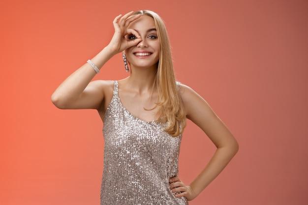 Очаровательная элегантная белокурая европейская беззаботная женщина в серебряном блестящем вечернем платье показывает без проблем, хорошо, знак, смотрит сквозь глаза, улыбается, восхищается, проверяет потрясающее промо, заинтриговано, красный фон.