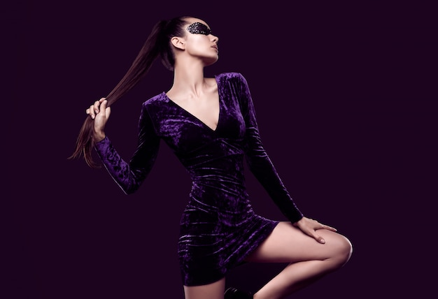 Charming elegant brunette woman in beautiful purple dress and sequins mask