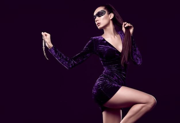 美しい紫色のドレスとスパンコールマスクで魅力的なエレガントなブルネットの女性