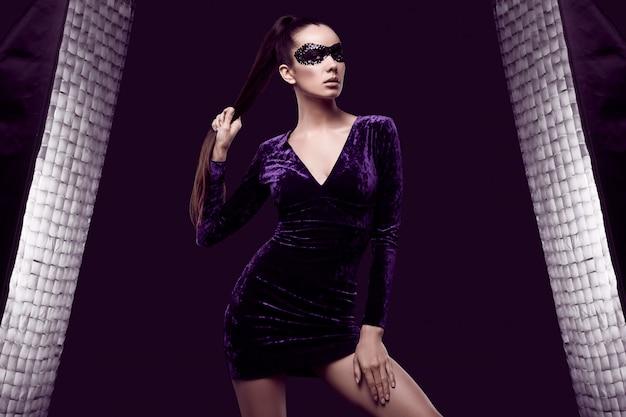 Очаровательная элегантная брюнетка в фиолетовом платье и маске с блестками
