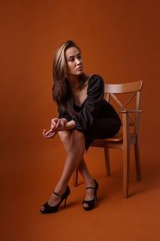 黒のドレス、ハイヒールの靴のポーズを身に着けている魅力的なエレガントなファッションモデル。アジアの若い女性はセクシーなイブニングドレスの椅子に座っています