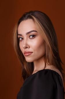 오렌지 배경에 포즈 검은 드레스를 입고 매력적인 우아한 패션 모델