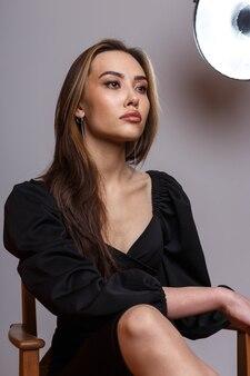 흰색 배경에 포즈 검은 드레스를 입고 매력적인 우아한 패션 모델