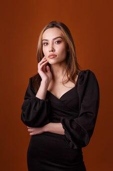 오렌지 배경에 포즈 깊은 목선과 검은 드레스를 입고 매력적인 우아한 패션 모델