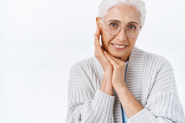 Charming, elegant and kind happy senior lady, grandmother with grey combed hair, wear glasses, tilt head cute and touch skin as apply anti-aging cream