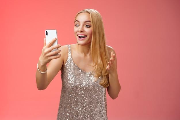 シルバーのドレスを着た魅力的なエレガントな素敵なブロンドの女の子がビデオ通話を話しているスマートフォンのディスプレイを見て面白がって驚いた