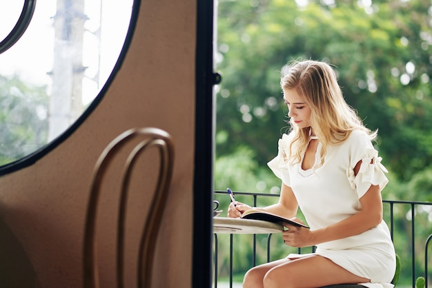 매력적인 우아한 젊은 금발의 여자가 카페 테이블에 앉아 그녀의 플래너 또는 저널을 작성