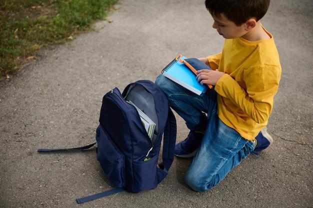 魅力的な小学生の男子生徒が公園の小道にひざまずいて、ノートと筆箱をバックパックに入れ、撮影後に帰宅