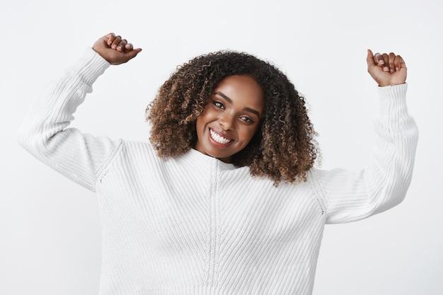 魅力的な活気に満ちたアクティブなポジティブな浅黒い肌のスポーツウーマンは、白い壁にセーターを着て明るい感じで広く踊りながら、喜びと娯楽で手を上げます