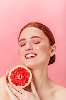 ジューシーなグレープフルーツを持っている魅力的なヨーロッパの女の子。ピンクの背景に目を閉じてポーズをとって柑橘類と幸せな笑う女性のスタジオショット。