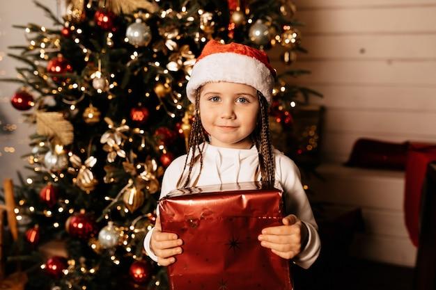 Affascinante ragazza europea che tiene i regali sopra l'albero di natale a casa
