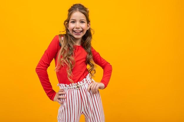 Очаровательная европейская девушка в красной блузке и полосатых штанах улыбается