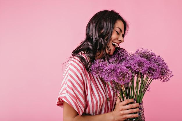 Affascinante ragazza europea con belle pose abbronzate con bracciata di tsatov lilla. closeup ritratto di signora in top bianco e rosa.