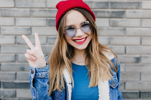Charming european woman in casual clothes posing with cute smile and peace sign. outdoor shot of elegant laughing girl in red hat.