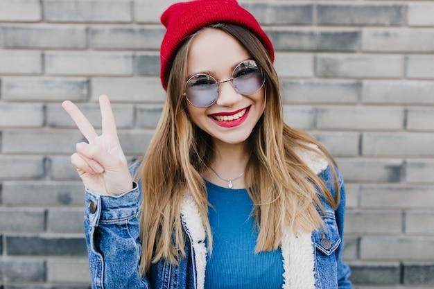かわいい笑顔とピースサインでポーズをとってカジュアルな服を着た魅力的なヨーロッパの女性。赤い帽子のエレガントな笑っている女の子の屋外ショット。