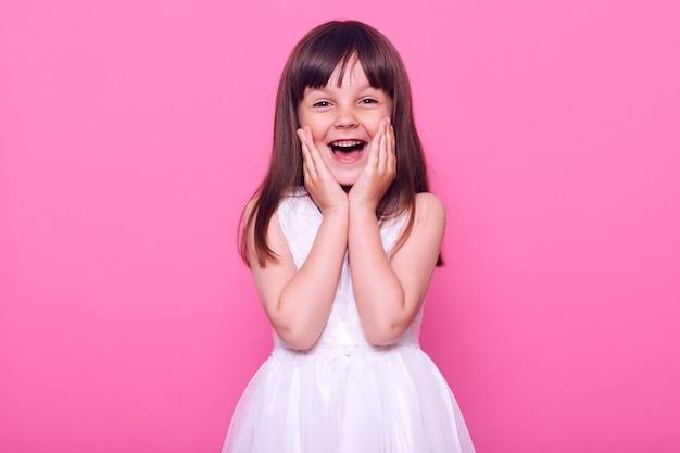 Очаровательная возбужденная женщина смотрит вперед со счастливым выражением лица, изумленная девочка, держащая ладони на щеках, в белом платье, изолированная на розовой стене