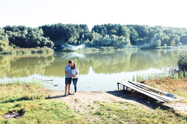 Charming expecting couple stands hugging by the green river