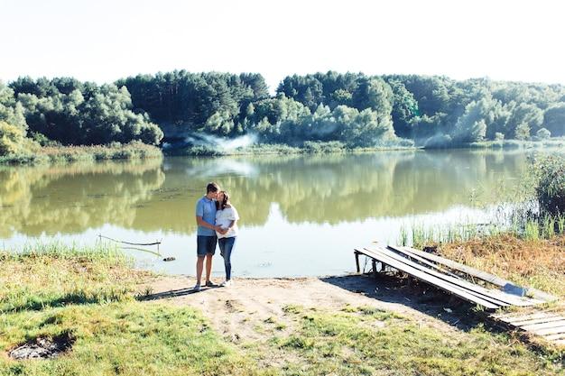 Очаровательная ожидающая пара стоит обниматься зеленой рекой