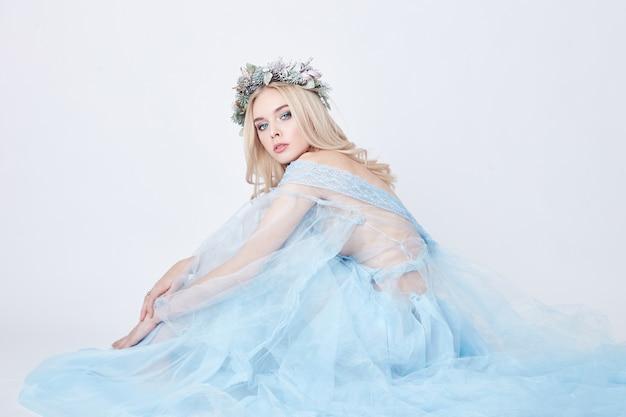 파란 천상의 드레스와 흰색 배경에 머리에 화환을 쓴 매력적인 요정 여자, 완벽한 피부와 화장을 한 부드럽고 신비한 금발 소녀. 청결, 바디 케어 및 피부