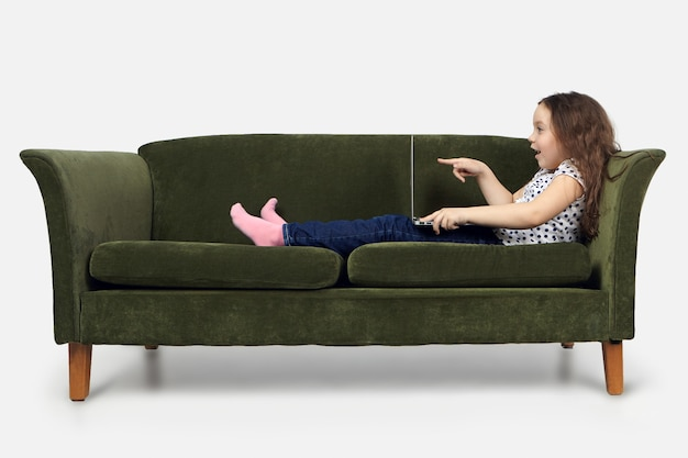 Очаровательный ребенок славы в повседневной одежде сидит на винтажном диване в помещении с ноутбуком на коленях, удивленно открывает рот и указывает пальцем на экран, с шокированным выражением лица