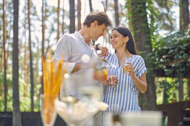 屋外で冷たい飲み物とガラスを保持している魅力的な女性とハンサムな男