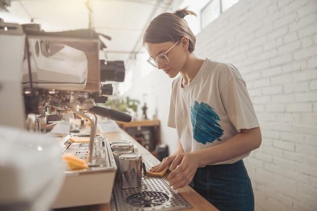 コーヒーショップの魅力的な女性のバリスタクリーニングカウンター