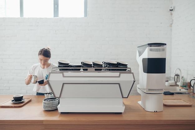 카페테리아에서 커피를 만드는 매력적인 여성 바리스타