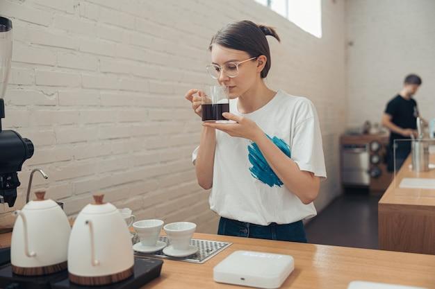 Очаровательная женщина-бариста, пахнущая кофе в кафетерии