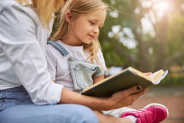 햇빛이 하루에 공원에서 아가씨와 함께 재미있는 책을 읽고 매력적인 여자 아이