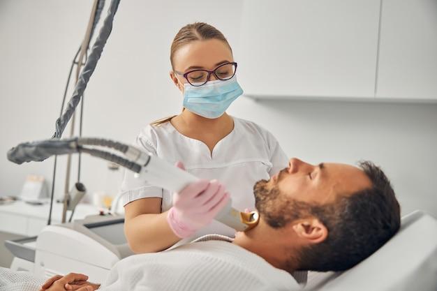 Charming female cosmetologist in medical mask removing unwanted hair from male neck with laser device