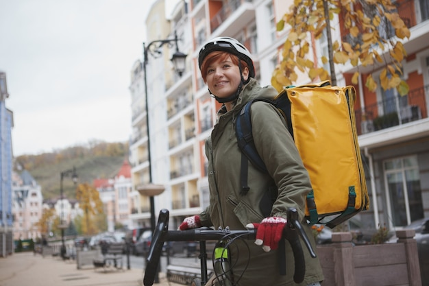 Charming female courier wearing biking helmet while working in the city on her bicycle