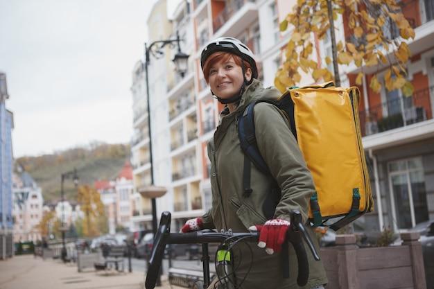 Очаровательная женщина-курьер в велосипедном шлеме во время работы в городе на своем велосипеде