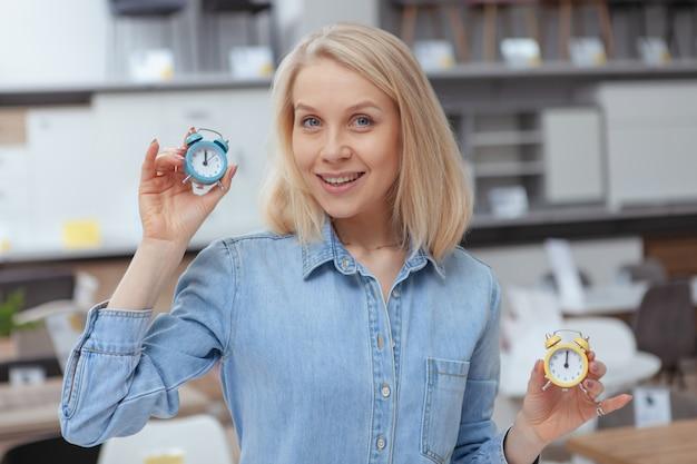 Очаровательная женщина-клиент улыбается и держит маленькие будильники, покупая товары для дома в универмаге