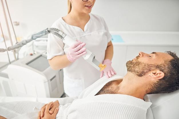 Charming female esthetician holding laser hair removal device and smiling while bearded young man lying on daybed