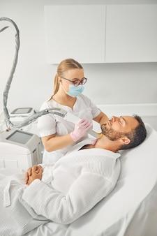 레이저 장치로 남성 목에서 원치 않는 머리카락을 제거하는 의료용 안면 마스크를 쓴 매력적인 여성 미용사