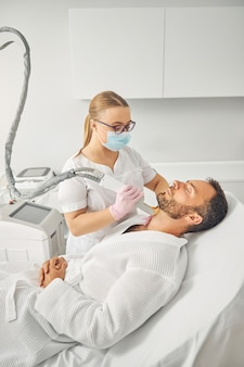 Charming female esthetician in medical face mask removing unwanted hair from male neck with laser device