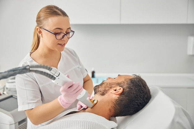 Charming female esthetician in sterile gloves removing unwanted hair from male neck with laser device