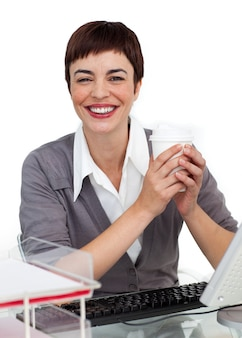 Charming female executive drinking a coffee at her desk