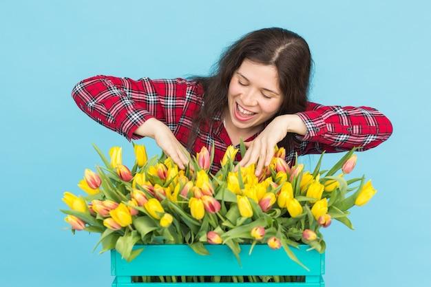 魅力的な女性の花屋が箱の中のチューリップを整理します