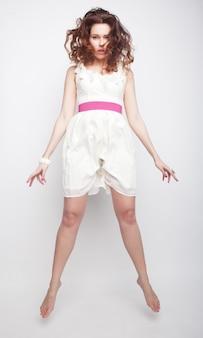 Очаровательная женщина в белом платье, перепрыгивая через серый фон